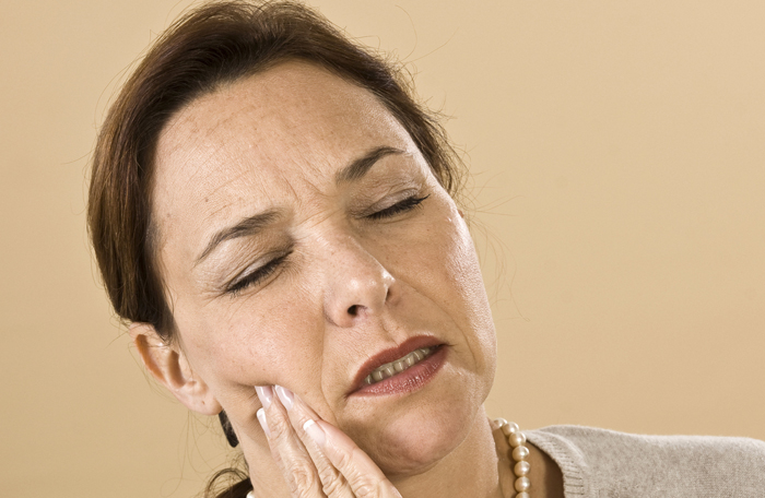 Woman in dental pain seeking relief from our dentist in Totowa NJ.