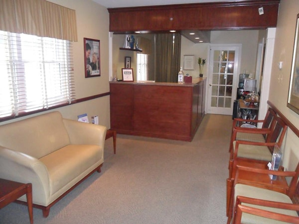Take the virtual office tour. This is the waiting room of Distinctive Dentistry in Totowa, NJ. Beautiful polished cherry wood reception desk and detailing with cream colored leather couch and chairs.