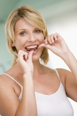 Woman flossing your teeth in honor of preventative dentistry in Totowa NJ