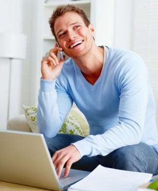 A smiling man on the computer, laughing on the phone after getting metal-free fillings