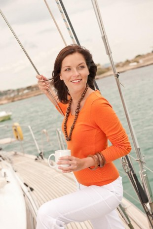 Woman on a sailing boat wearing an orange shirt holding a coffee cup after receiving general dentistry in Totowa, NJ