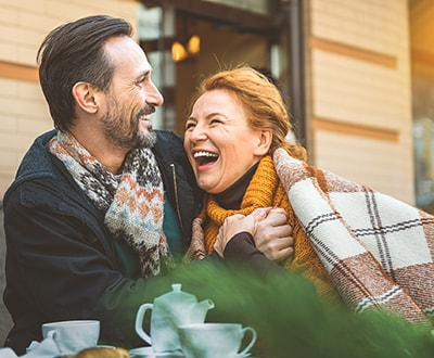 A happy couple laughing and snuggled in a blanket after receiving high-quality Totowa Dental Services