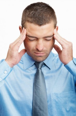 A man who is rubbing his temples, suffering from a headache. TMJ Treatment can help.
